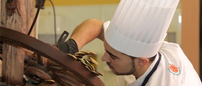 Participante del trofeo elaborando escultura de chocolate