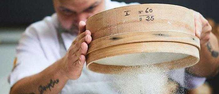 Panadero tamizando harina