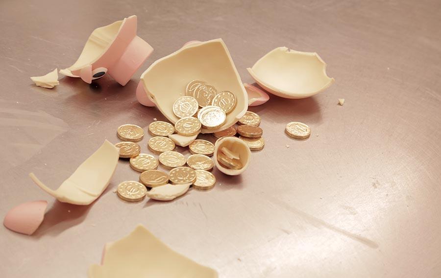 El cerdito de chocolate roto muestra las monedas en el interior