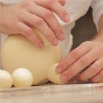 Cuando ya ha reducido el huevo a la altura adecuada, lo pega para formar una de las patas del cerdito